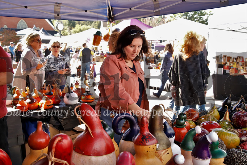 Kristen Zappa looks through dried gourd artworks by Steve Miller at Mars' Apple Fest Saturday. Seb Foltz/Butler Eagle