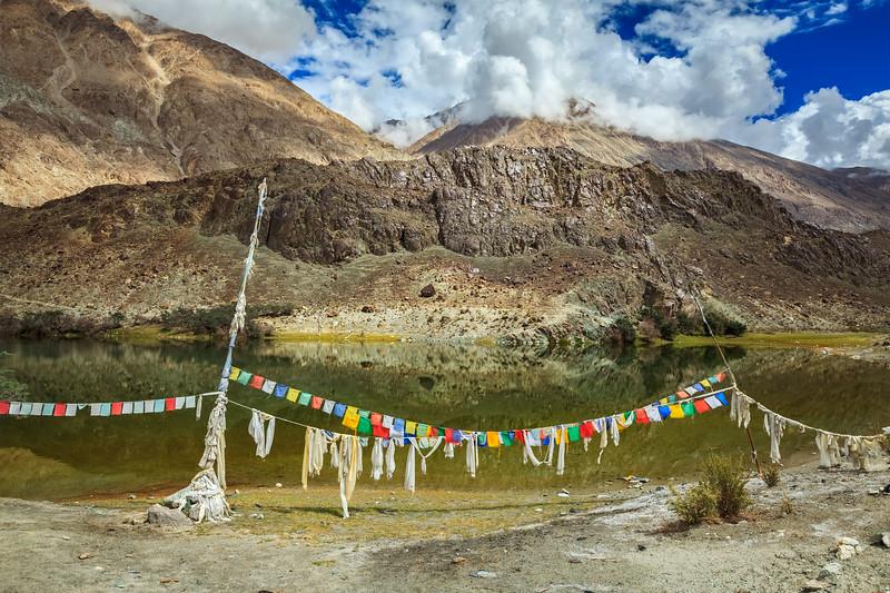 Buddhist prayer flags (lungta) at Lohan Tso - Buddhist sacred holy lake in Himalayas.  Nubra Valley, Ladakh, India