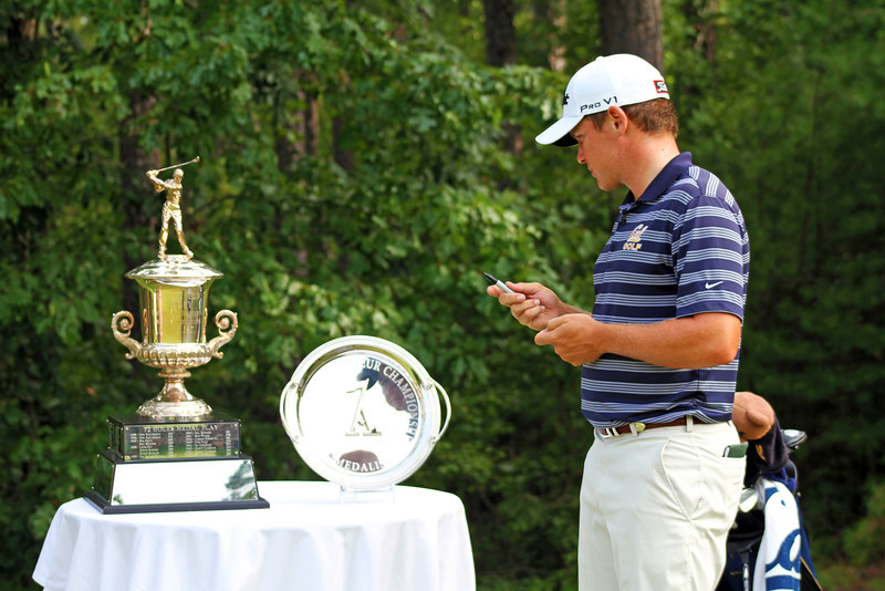 Michael Weaver of Fresno, CA takes a peek at the medalist trophies on the first tee while he marks his ball before the fourth round of stroke play at the 2013 Western Amateur at The Alotian Club in Roland, AR. (WGA Photo/Gary Holaway)