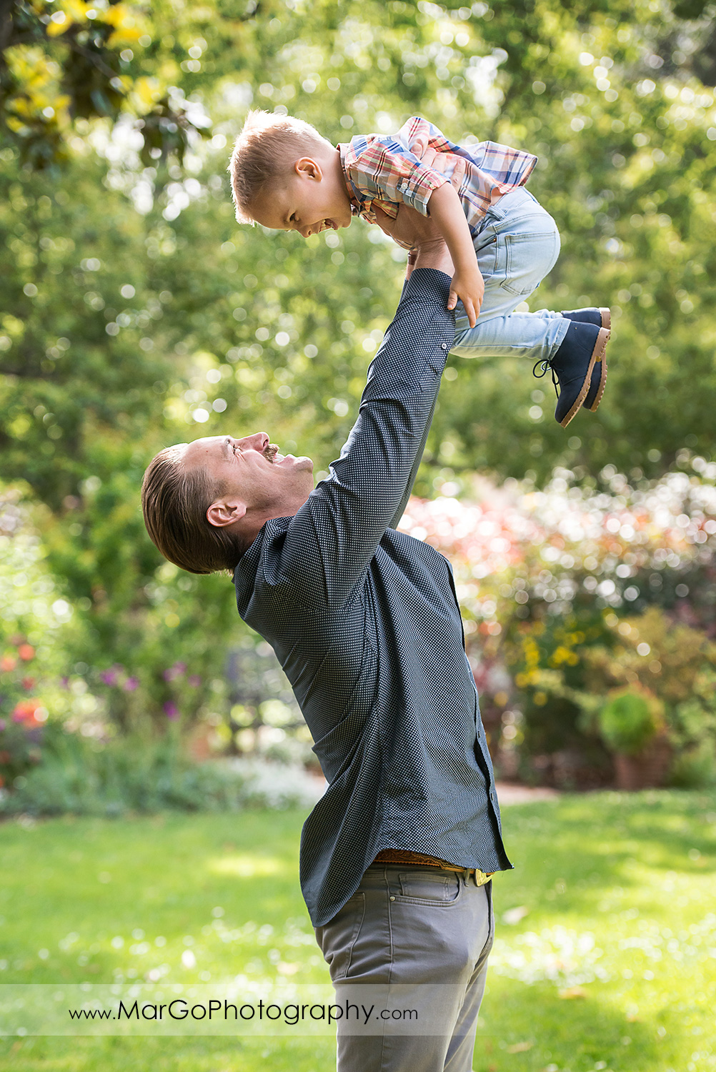 man in grey shirt lifting up little boy in Shinn Historical Park and Arboretum in Fremont