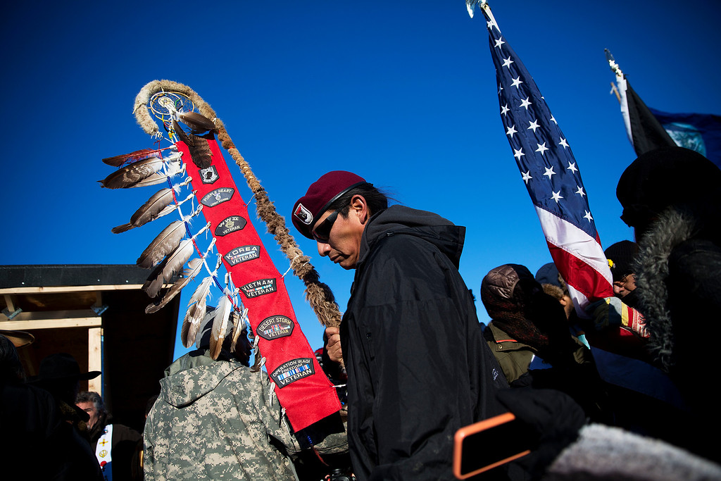 . Native American veterans join an interfaith ceremony at the Oceti Sakowin camp where people have gathered to protest the Dakota Access oil pipeline in Cannon Ball, N.D., Sunday, Dec. 4, 2016. Tribal elders have asked the military veterans joining the large Dakota Access pipeline protest encampment not to have confrontations with law enforcement officials, an organizer with Veterans Stand for Standing Rock said Sunday, adding the group is there to help out those who\'ve dug in against the four-state, $3.8 billion project. (AP Photo/David Goldman)