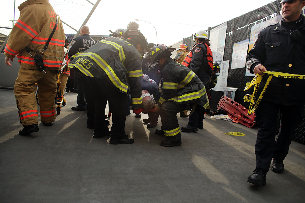 Description of . An injured person is carried to a waiting ambulance following an early morning ferry accident during rush hour in Lower Manhattan on January 9, 2013 in New York City. About 50 people were injured in the accident, which left a large gash on the front side of the Seastreak ferry at Pier 11.  (Photo by Spencer Platt/Getty Images)