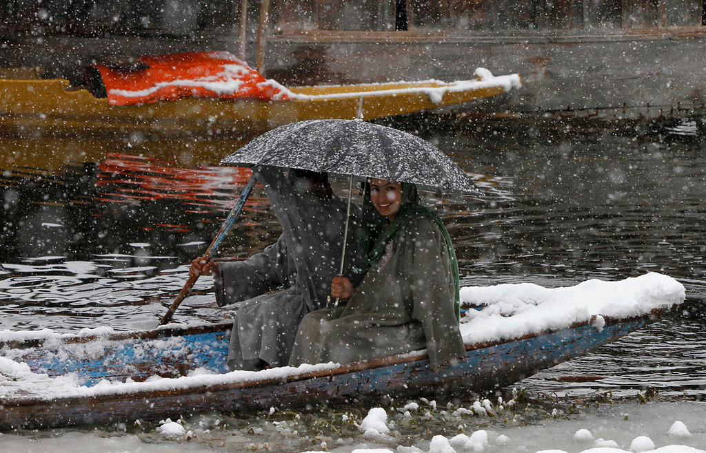 . Kashmiris cross the Dal Lake in snow in Srinagar, India, Tuesday, Dec. 31, 2013. Snowfalls in the Indian portion of Kashmir has disrupted power supply, air traffic and road traffic between Srinagar and Jammu, the summer and winter capitals of India\'s Jammu-Kashmir state, according to news reports. (AP Photo/Mukhtar Khan)