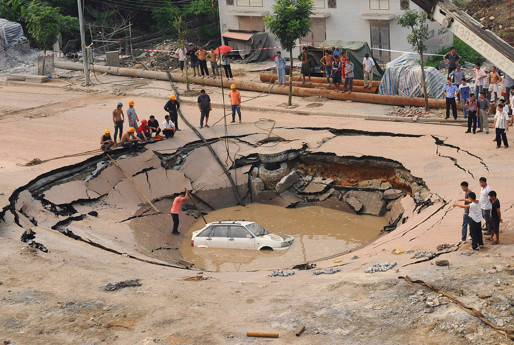 . A stranded car is hoisted from a collapsed road surface in Guangzhou, Guangdong province, September 7, 2008. The road collapsed and trapped the car in a hole, which measured 5 meters (16.4 feet) in depth and 15 meters (49.2 feet) in diameter, local media reported. Further investigation is underway. Picture taken September 7, 2008. REUTERS/China Daily