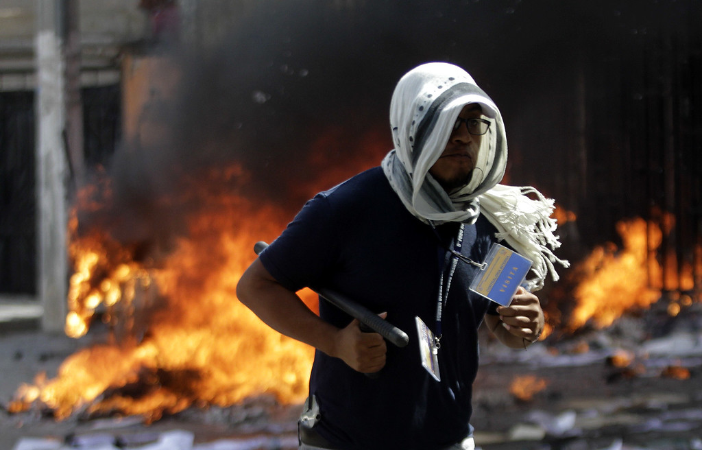 . A protester is seen in front of fire at the Education Secretarariat\'s Finance Office in Chilpancingo, Guerrero State, Mexico on November 12, 2014. Pedro PARDO/AFP/Getty Images