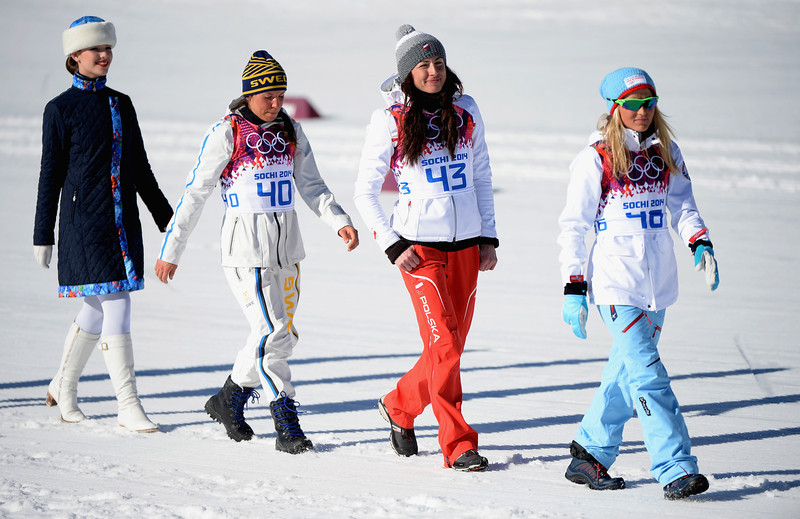 . (2L-R) Silver medalist Charlotte Kalla of Sweden, gold medalist Justyna Kowalczyk of Poland and bronze medalist Therese Johaug of Norway are escorted to the podium during the flower ceremony for the Women\'s 10 km Classic during day six of the Sochi 2014 Winter Olympics at Laura Cross-country Ski & Biathlon Center on February 13, 2014 in Sochi, Russia.  (Photo by Harry How/Getty Images)