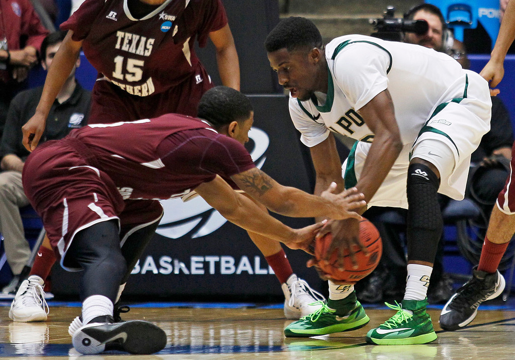 . Texas Southern guard Madarious Gibbs, left, and Cal Poly guard Dave Nwaba chase a loose ball in the first half of a first-round game of the NCAA college basketball tournament on Wednesday, March 19, 2014, in Dayton, Ohio. (AP Photo/Skip Peterson)