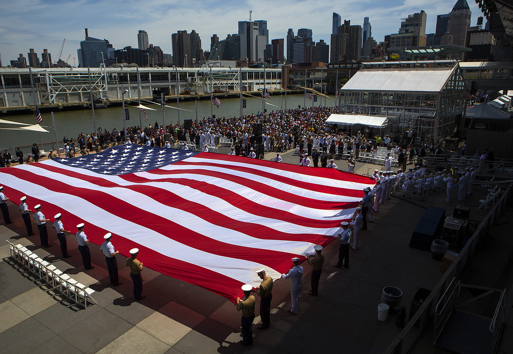 . Members of the military unfurl an American flag during a wreath laying ceremony at the Intrepid Sea, Air & Space Museum May 26 in New York City. Memorial Day, orginally celebrated as Decoration Day after the Civial War in 1868, became a federal holiday in 1971 and commemorates all those who have died fighting for the U.S. in wars.  (Photo by Eric Thayer/Getty Images)