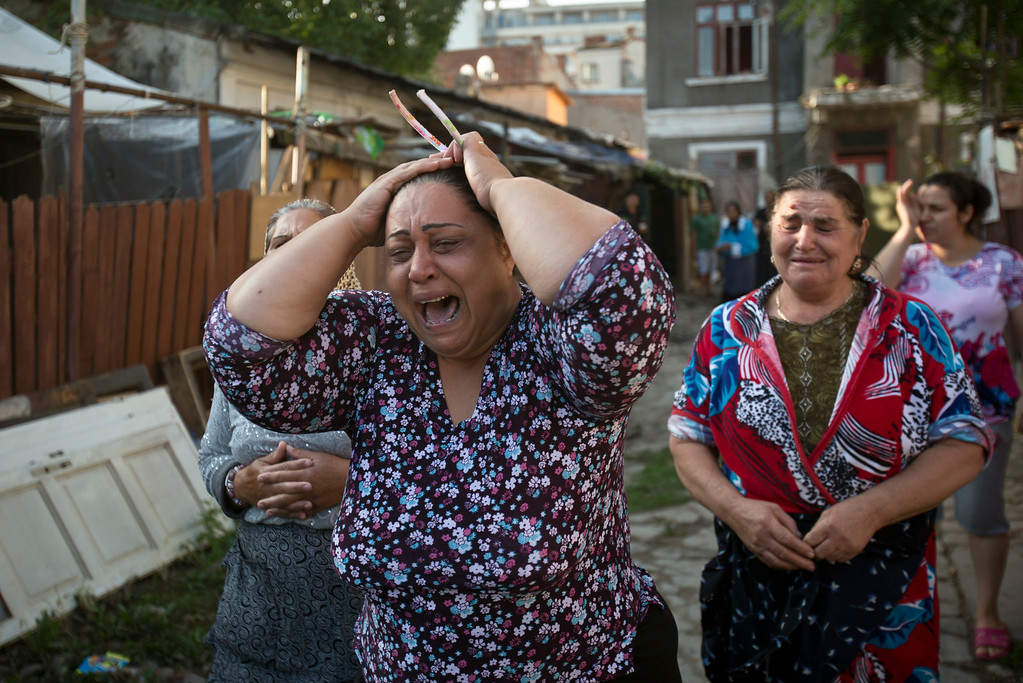 . Roma women cry as riot police arrive to assist in the eviction of more than 100 people from their homes in Bucharest, Romania, Monday, Sept. 15, 2014. (AP Photo/Vadim Ghirda)