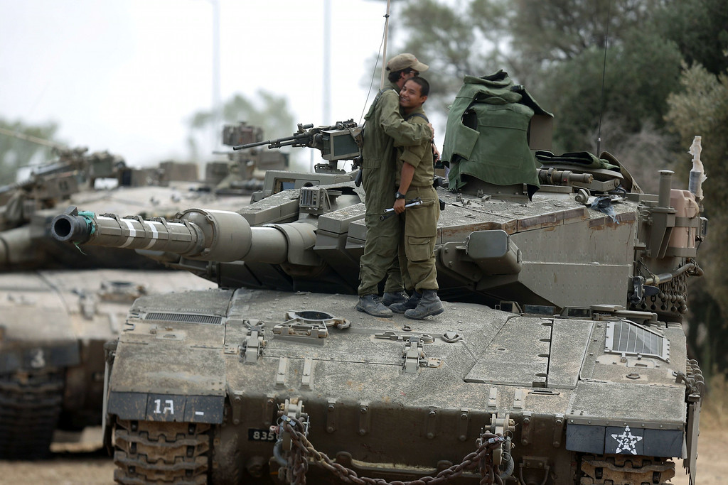 . Israeli soldiers hug as they stand on a Merkava tank, at an army deployment area near Israel\'s border with the Gaza Strip, on July 17, 2014. Israel and the Islamist Hamas movement have agreed on a ceasefire that will begin at 0300 GMT on Friday, an Israeli official told AFP. AFP PHOTO /MENAHEM KAHANA/AFP/Getty Images