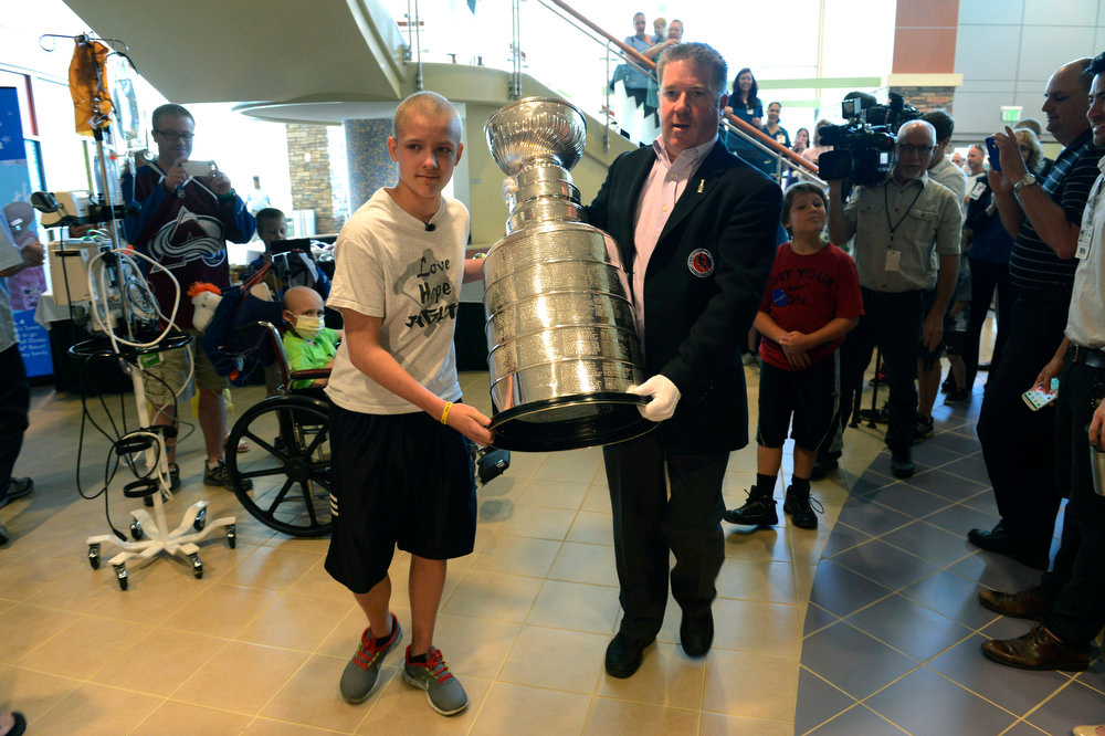 . Keeper of the Cup, Mike Bolt, and Logan Piz, 13, left, carry the Stanley Cup through the lobby at Rocky Mountain Hospital for Children in Denver, CO May 15, 2013. The hospital, Make-A-Wish, Discover and the National Hockey League teamed up to grant  Logan\'s wish to spend a day with the Stanley Cup and share it with friends, family and supporters. Logan has not played hockey since he was diagnosed with Ewing�s sarcoma in November 2012. Joining Logan were his mother and father, Tammy and Ron and his brother, Hayden, 9.  (Photo By Craig F. Walker/The Denver Post)
