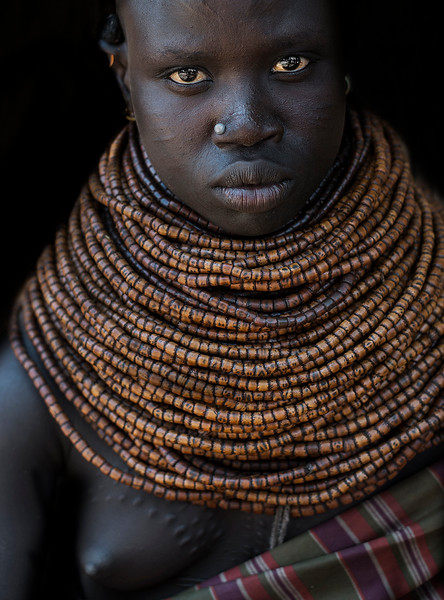 A young woman from the Nyangatom tribe. Even though most women now ware colorful plastic necklaces this lady has a traditional one made from animal bone.  Omo Valley, Ethiopia, 2017