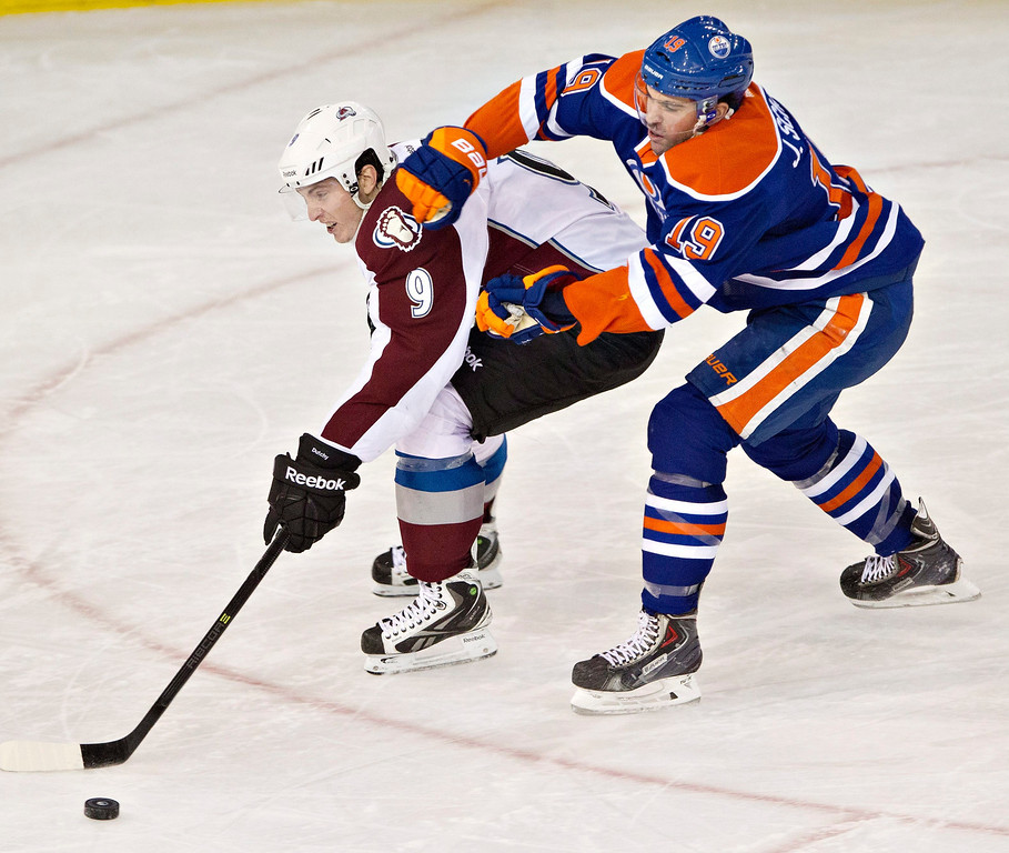 . Colorado Avalanche\'s Matt Duchene (9) is chased down by Edmonton Oilers\' Justin Schultz (19) during second-period NHL hockey game action in Edmonton, Alberta, Thursday, Dec. 5, 2013. (AP Photo/The Canadian Press, Jason Franson)