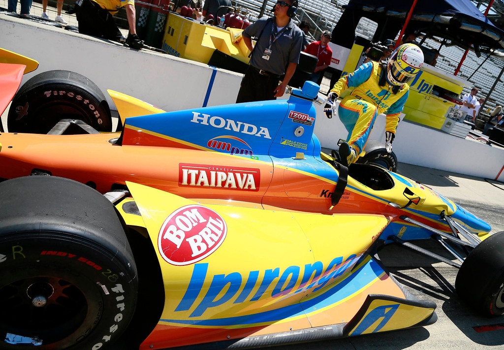 . Dale Coyne Racing driver Ana Beatriz (R) of Brazil climbs into her race car during a practice session at the Indianapolis Motor Speedway in Indianapolis, Indiana May 15, 2013. The 97th running of the Indianapolis 500 is scheduled for May 26.  REUTERS/Brent Smith