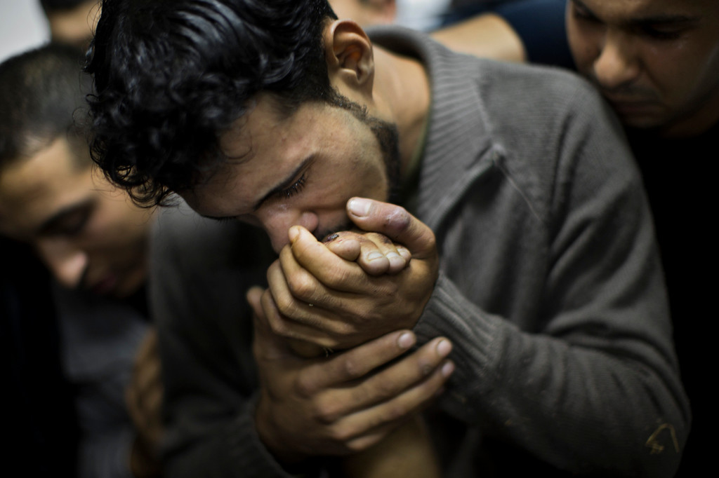 . A Palestinian man kisses the hand of a dead relative in the morgue of Shifa Hospital in Gaza City, Sunday, Nov. 18, 2012. President Barack Obama on Sunday defended Israel\'s airstrikes on the Gaza Strip, but he warned that escalating the offensive with Israeli ground troops could deepen the death toll and undermine any hope of a peace process with the Palestinians. (AP Photo/Bernat Armangue)