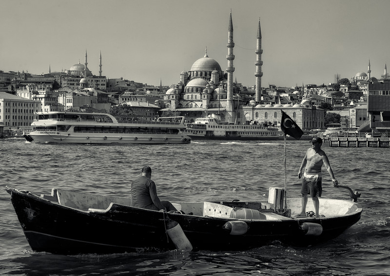 Fishermen on the Golden Horn with the Yeni Cani mosque in the background.  Istanbul, Turkey, 2016.