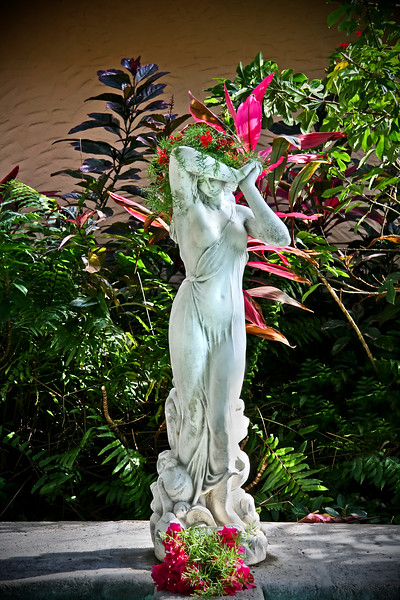 Statue of women with her hands together and a flower piece on top of her head, with beautiful flowers and plants surrounding.