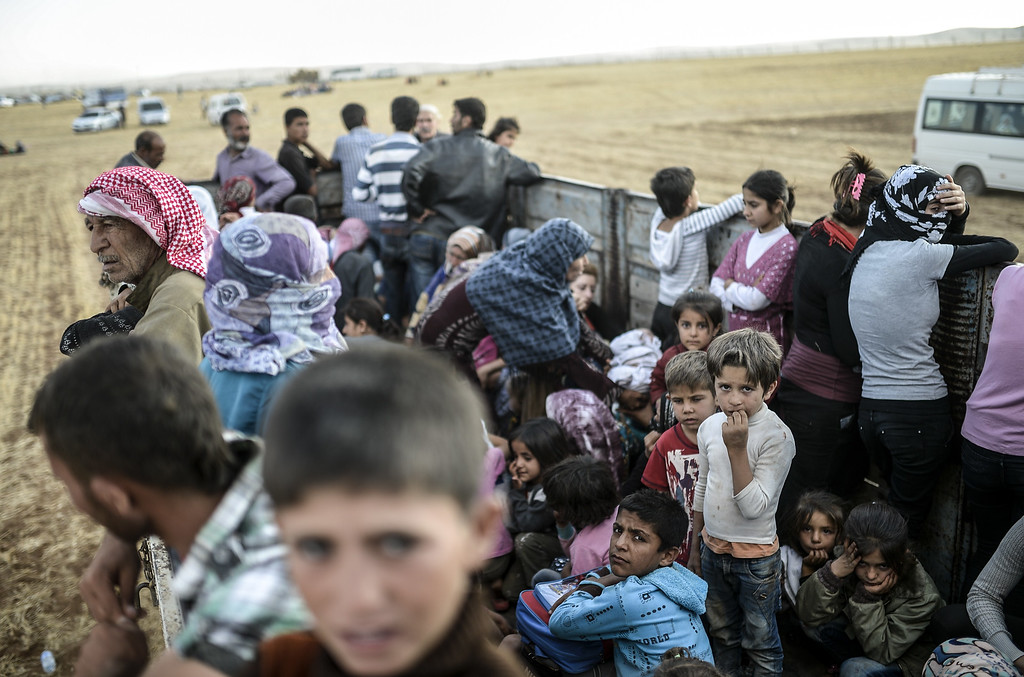 . Syrian Kurds wait near the Syrian border at the southeastern town of Suruc in Sanliurfa province, on September 20, 2014. Tens of thousands of Syrian Kurds flooded into Turkey on September 20, fleeing an onslaught by the jihadist Islamic State group that prompted an appeal for international intervention.  BULENT KILIC/AFP/Getty Images