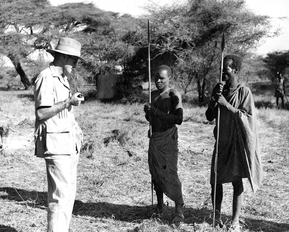. FEB 23 1950  White hunter or guide Frank Bowman issues directions in Swahili to the two native Turkana trackers, key men in any African safari. The natives carry spears constantly, not only as pro­tection from lions but for cutting food, skinning and dozens of other tasks.  Credit: Denver Post