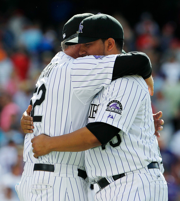 . Colorado Rockies starting pitcher Jhoulys Chacin, right, hugs pitching coach Jim Wright after Chacin pitched 8-and-2/3s innings against the Philadelphia Phillies to lead the Rockies to a 5-2 victory in  a baseball game in Denver on Sunday, June 16, 2013. (AP Photo/David Zalubowski)
