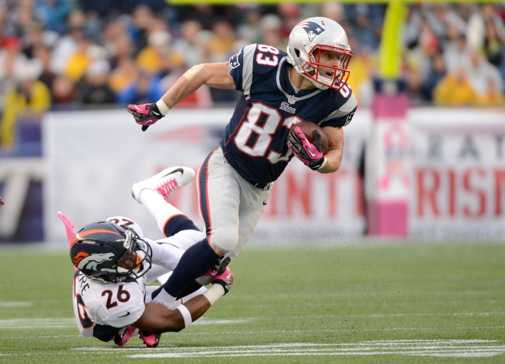 . Denver Broncos free safety Rahim Moore (26) grabs New England Patriots wide receiver Wes Welker (83) by the ankles for a tackle during the first quarter Sunday, September 7, 2012 at Gillette Stadium.  John Leyba, The Denver Post