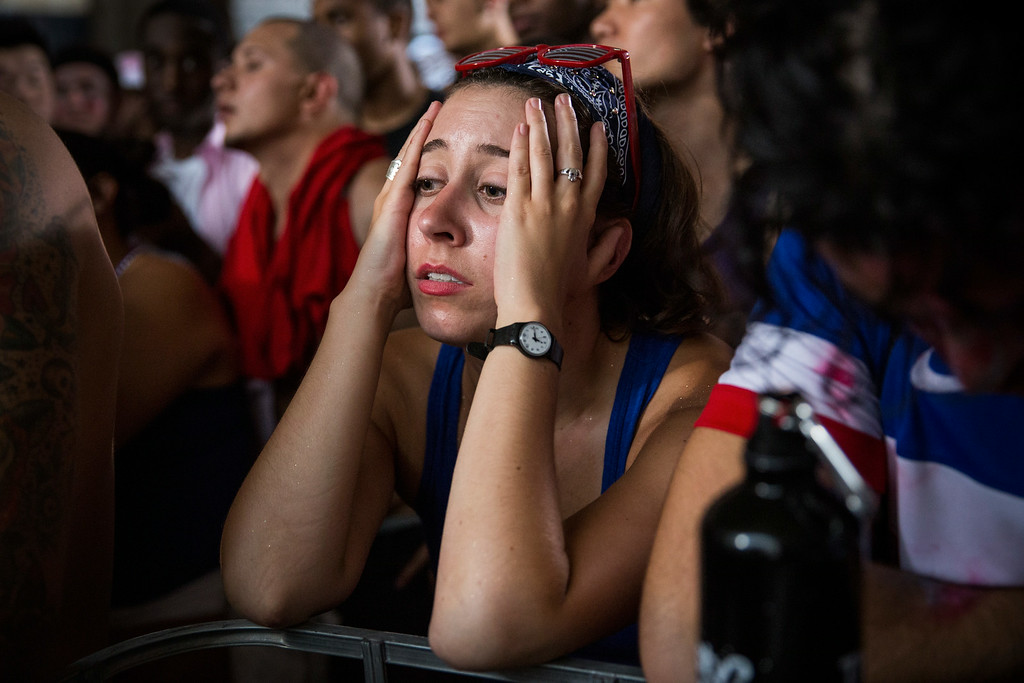 . Margaret Deli, of New Haven, CT, reacts as Belgium scores a goal against the United States in the World Cup while watching on a projected screen under the Manhattan Bridge on July 1, 2014 in the Dumbo neighborhood of the Brooklyn borough of New York. Belgium went on to eleminate the US from the World Cup in overtime with a final score 2-1.  (Photo by Andrew Burton/Getty Images)