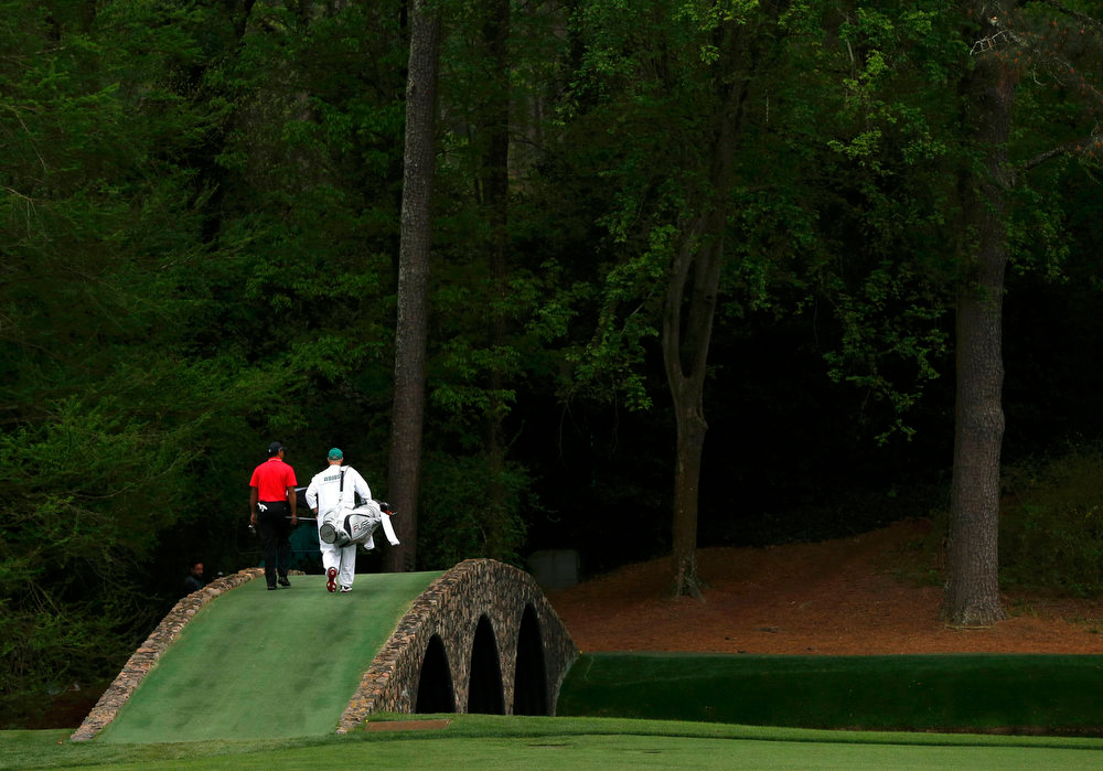 Description of . Tiger Woods of the U.S. walks over the Hogan Bridge with caddie Joe LaCava to the 12th green during final round play in the 2013 Masters golf tournament at the Augusta National Golf Club in Augusta, Georgia, April 14, 2013. REUTERS/Phil Noble