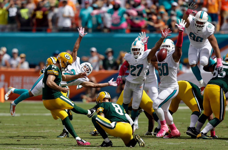 . Green Bay Packers kicker Mason Crosby (2) boots a field goal as punter Tim Masthay (8) holds during the first half of an NFL football game against the Miami Dolphins, Sunday, Oct. 12, 2014, in Miami Gardens, Fla. (AP Photo/Wilfredo Lee)