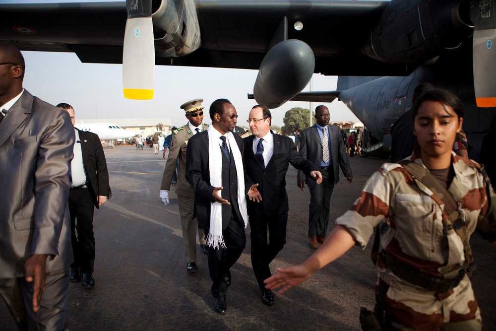 Description of . French President Francois Hollande, center right, talks with Mali\'s President Dioncounda Traore, center left, as Hollande arrives at the airport in Sevare, Mali, en route to Timbuktu, Saturday, Feb. 2, 2013. Hollande landed Saturday in the fabled Malian town of Timbuktu, making a triumphant stop six days after French forces parachuted in to liberate the desert city from the rule of al-Qaida-linked militants. (AP Photo/Malin Palm)