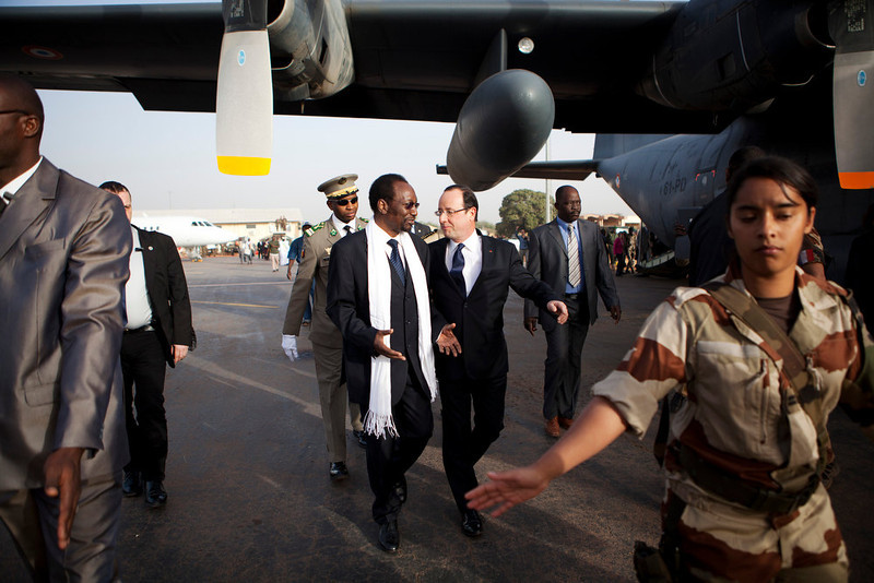 . French President Francois Hollande, center right, talks with Mali\'s President Dioncounda Traore, center left, as Hollande arrives at the airport in Sevare, Mali, en route to Timbuktu, Saturday, Feb. 2, 2013. Hollande landed Saturday in the fabled Malian town of Timbuktu, making a triumphant stop six days after French forces parachuted in to liberate the desert city from the rule of al-Qaida-linked militants. (AP Photo/Malin Palm)