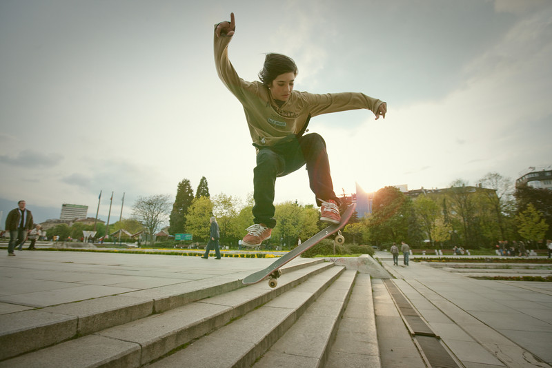 A bunch of kids skateboarding in Sofia.   I am generally pretty apprehensive about asking people to take their photos. Especially people here in Bulgaria. Everyone things you are trying to extort them or something and that their computer will end up all over there internet (as if that is a bad thing). They just wish they were that important.   Anyways these kids were the opposite. They saw my camera and came running up asking if I would take pictures of them. I feel kind of bad because I told them they would be up on my site withing a week. That was almost three months ago. O well. Here they finally are kid.