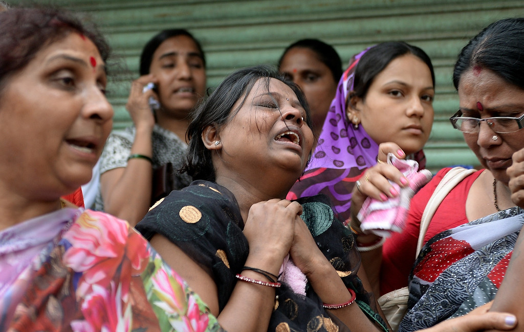 . Relatives cry as they wait near the site of a building collapse in Mumbai on September 27, 2013.   AFP PHOTO/ PUNIT  PARANJPE/AFP/Getty Images