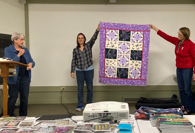 Jackie Borszich showing us a butterfly fabric quilt.