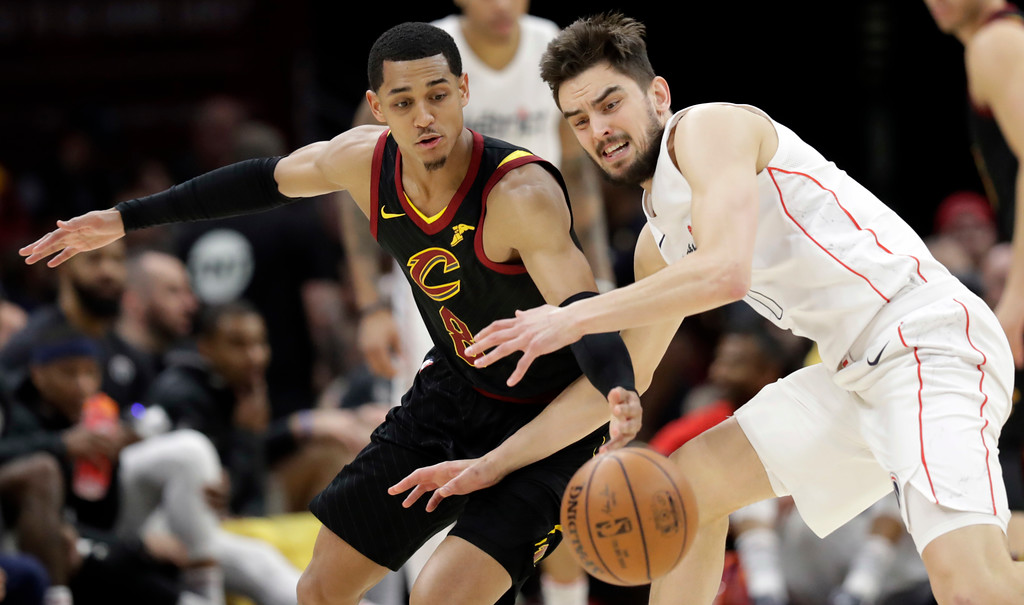 . Cleveland Cavaliers\' Jordan Clarkson, left, and Washington Wizards\' Tomas Satoransky, from the Czech Republic, battle for the ball in the first half of an NBA basketball game, Thursday, April 5, 2018, in Cleveland. (AP Photo/Tony Dejak)