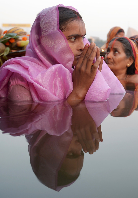 . Indian Hindu devotees perform rituals as they worship the setting sun during Chhath Puja while standing in a water body in Kolkata on November 8, 2013.     AFP PHOTO/Dibyangshu SARKAR/AFP/Getty Images