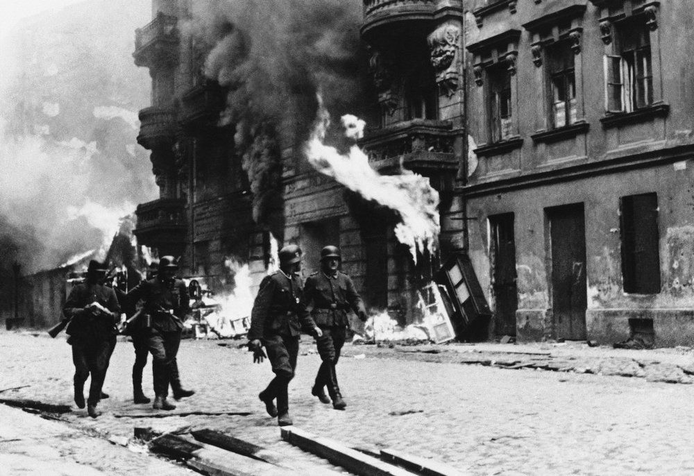 . Nazi officers stroll through the streets as buildings in the Warsaw Ghetto, Poland, burn out of control, as the ghetto is destroyed, spring 1943.  (AP Photo)