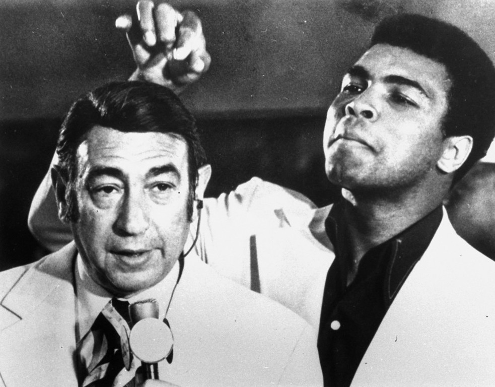 . Muhammad Ali, former world heavyweight boxing champion, toys with the finely combed hair of television sports commentator Howard Cosell before the start of the Olympic boxing trials, August 7, 1972, in West Point, N.Y.  (AP Photo/Joe Caneva)