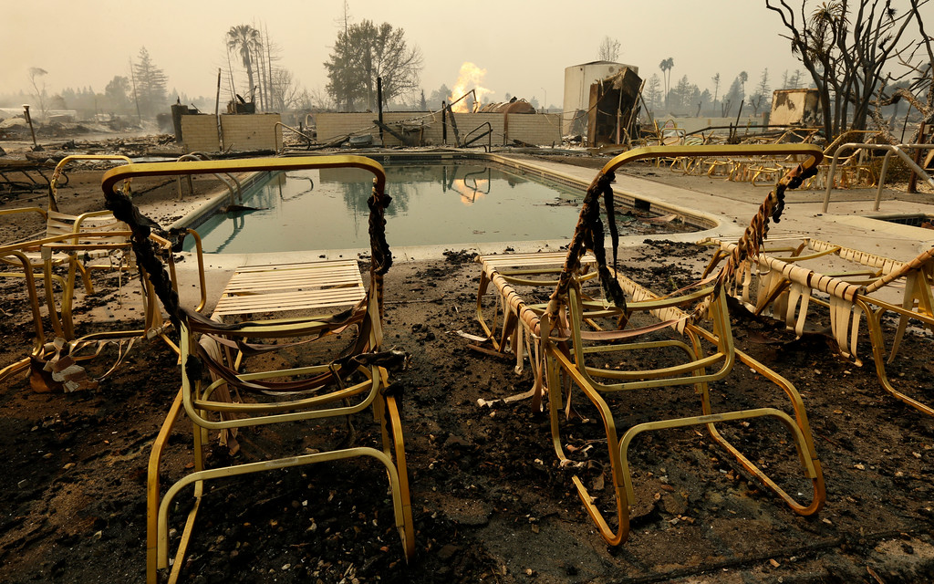 . Fire burns from an open gas valve near the pool area at the Journey\'s End mobile home park on Monday, Oct. 9, 2017, in Santa Rosa, Calif. Wildfires whipped by powerful winds swept through Northern California early Monday, sending residents on a headlong flight to safety through smoke and flames as homes burned. (AP Photo/Ben Margot)