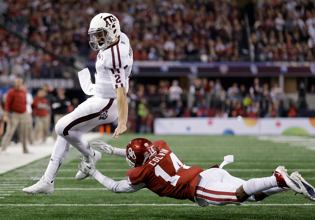 . Texas A&M quarterback Johnny Manziel is run out of bounds by Oklahoma \'s Aaron Colvin (14) during the second half of the Cotton Bowl NCAA college football game Friday, Jan. 4, 2013, in Arlington, Texas. (AP Photo/LM Otero)