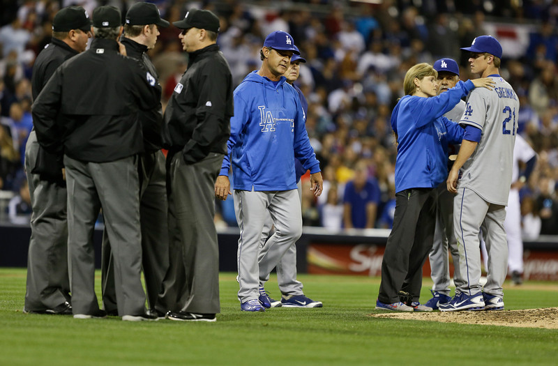 . Los Angeles Dodgers pitcher Zack Greinke is attended to by the team trainer Sue Falsone as manager Don Mattingly looks on during an interlude of a braw that started when Greinke hit San Diego Padres\' Carlos Quentin with a pitch in the sixth inning of baseball game in San Diego, Thursday, April 11, 2013. The battle restarted moments later. (AP Photo/Lenny Ignelzi)