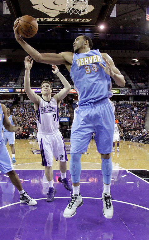 . Denver Nuggets center JaVale McGee, right, grabs a rebound in front of    Sacramento Kings guard Jimmer Fredette, during the fourth quarter of an NBA basketball game in Sacramento, Calif., Sunday, Dec. 16, 2012.  The Nuggets won 122-97.(AP Photo/Rich Pedroncelli)