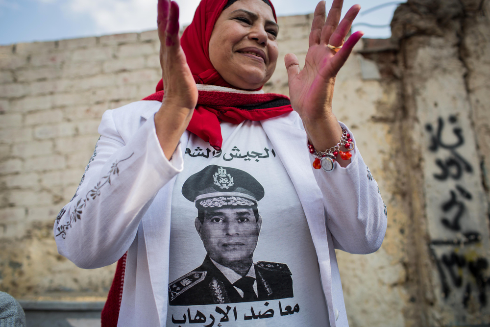 ". An Egyptian woman wears a t-shirt with a photo of Egypt\'s Defense Minister, Gen. Abdel-Fattah el-Sissi outside a polling station on the first day of voting in the country\'s constitutional referendum in Cairo, Egypt, Tuesday, Jan. 14, 2014. Upbeat and resentful of the Muslim Brotherhood, Egyptians voted Tuesday on a new constitution in a referendum that will pave the way for a likely presidential run by the nation\'s top general months after he ousted Islamist President Mohammed Morsi. Arabic on her shirt reads, ""the military and the people together against terrorism.\""(AP Photo/Eman Helal)"