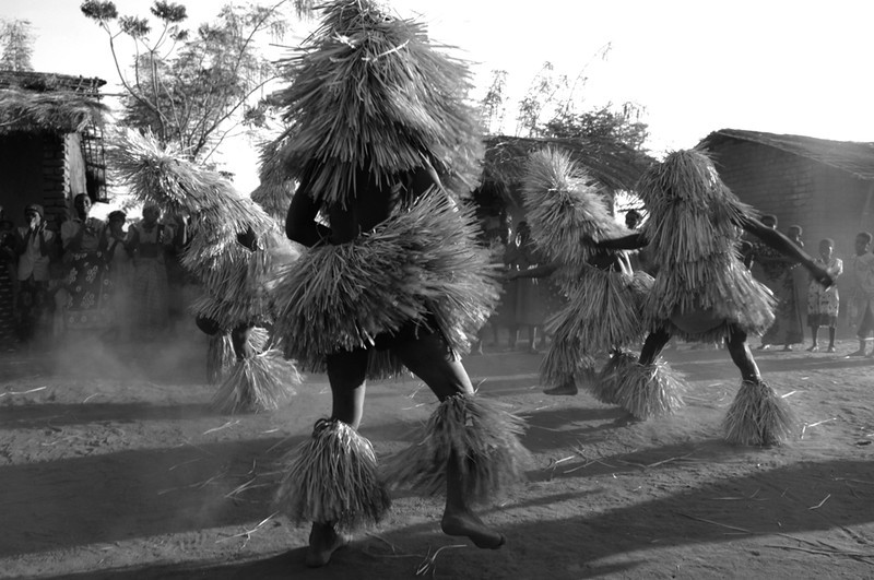 """Counselors from a Yao circumcision camp dance in the nearby village as a form of comfort and entertainment for the worried parents and realtives of the boys. Parents are not allowed to see their sons while the boys are sequestered in the exclusive camp during """"jando"""", the Yao circumcision ceremony that marks the male passage into adulthood. Seeing the dancers from the encampment reassures everyone that everything is fine and the boys are doing well. Salima, Malawi. August 8, 2006"""