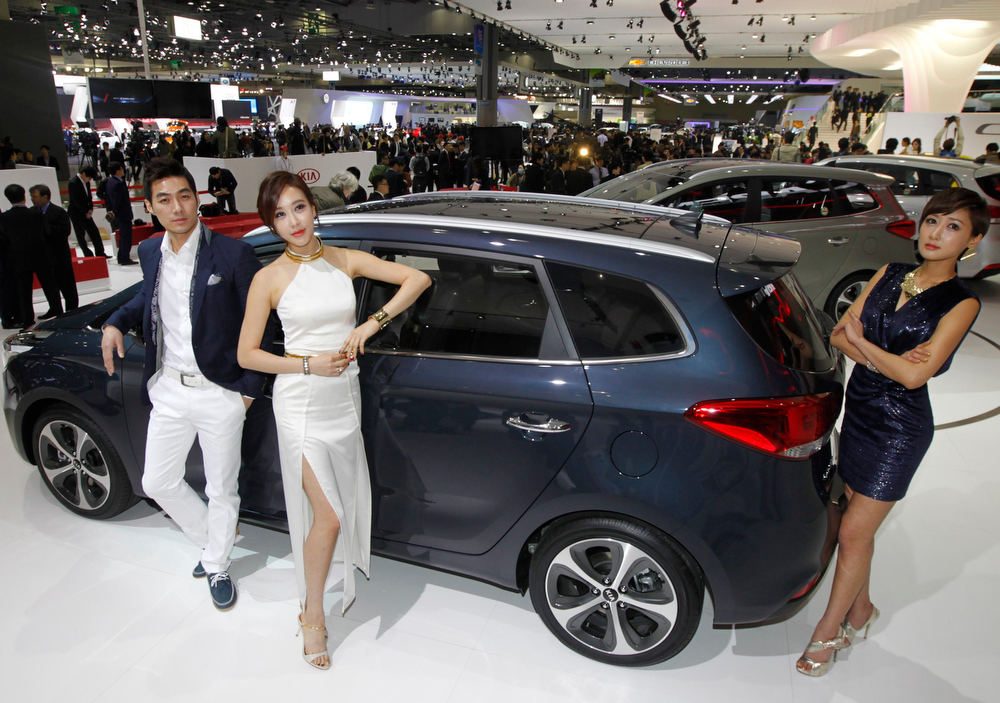. Models pose next to Kia Motors\' Carens at the Seoul motor show in Goyang, north of Seoul March 28, 2013. South Korea\'s Kia Motors is worried about the sharp decline in the value of the yen, which is aiding Japanese rivals, an executive at the affiliate of Hyundai Motor said on Thursday. REUTERS/Lee Jae-Won