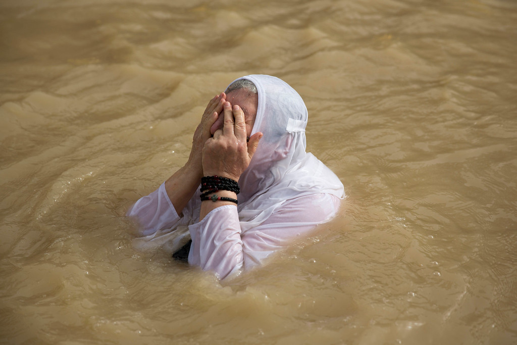 . A Christian Orthodox pilgrim prays after she was baptized during the traditional Epiphany baptism ceremony at the Qasr-el Yahud baptism site in the Jordan river near the West Bank town of Jericho, Monday, Jan. 18, 2016.  The site is traditionally believed by many to be the place where Jesus was baptized. (AP Photo/Ariel Schalit)