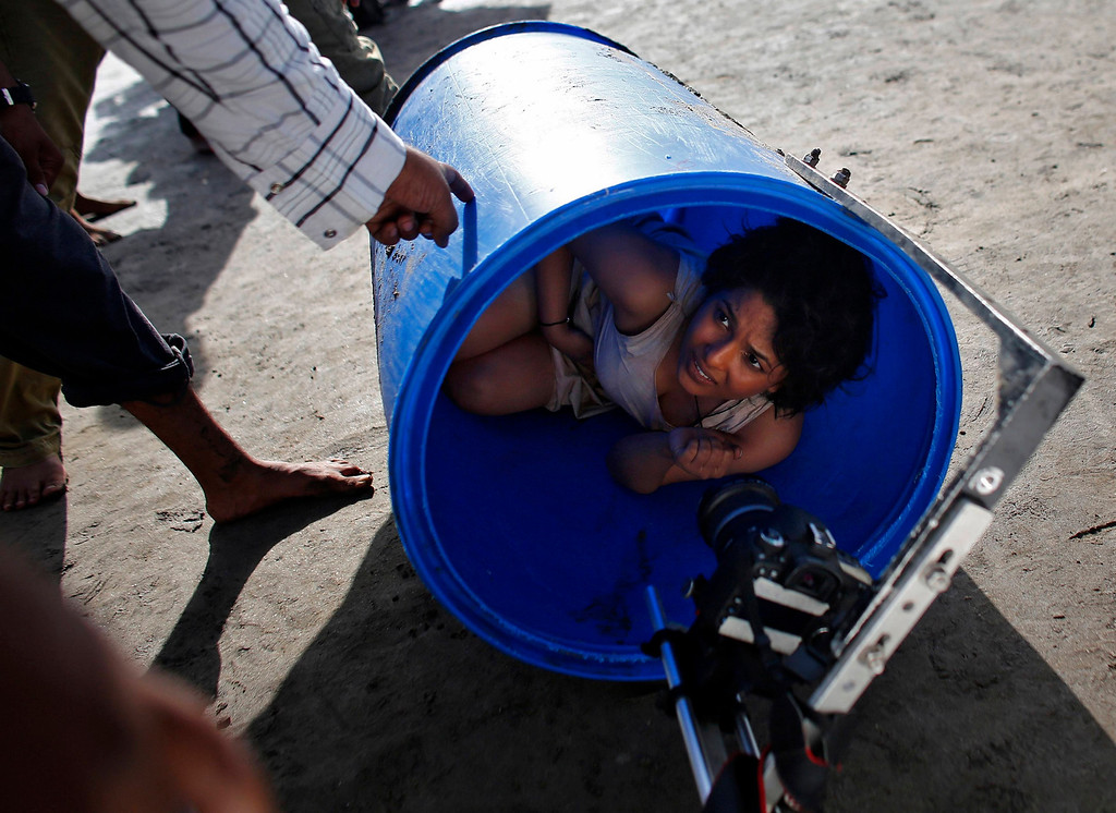 """. Bollywood actress Chitrashi Rawat lies in a plastic drum as she is briefed by a crew member during the shoot for the film \'Black Home\' at a beach on the outskirts of Mumbai April 26, 2013. Indian cinema marks 100 years since Dhundiraj Govind Phalke\'s black-and-white silent film \""""Raja Harishchandra\"""" (King Harishchandra) held audiences spellbound at its first public screening on May 3, 1913, in Mumbai. Indian cinema, with its subset of Bollywood for Hindi-language films, is now a billion-dollar industry that makes more than a thousand films a year in several languages. It is worth 112.4 billion rupees (over $2 billion) and leads the world in terms of films produced and tickets sold. Picture taken April 26, 2013. REUTERS/Danish Siddiqui"""