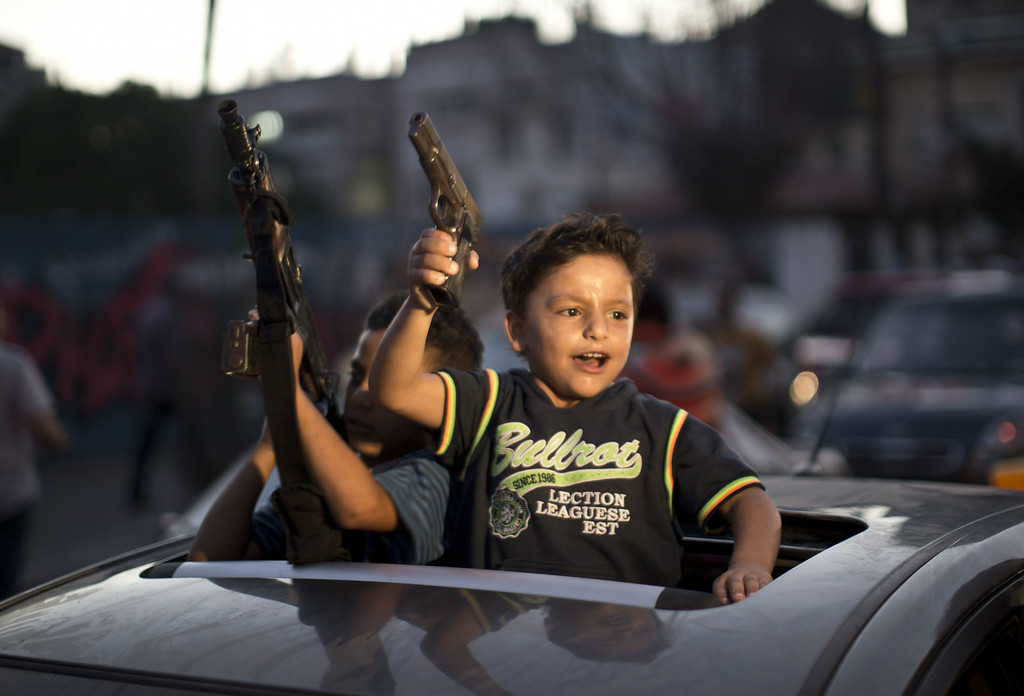 """. Children hold up guns (one with an empty magazine) from a car as Palestinians gather in the streets to celebrate after a deal had been reached between Hamas and Israel over a long-term end to seven weeks of fighting in the Gaza Strip on August 26, 2014 in Gaza City. Israel has agreed to observe an \""""unlimited\"""" ceasefire in the Gaza Strip, a senior official told AFP on Tuesday, shortly after the deal was announced by the Palestinians. MAHMUD HAMS/AFP/Getty Images"""