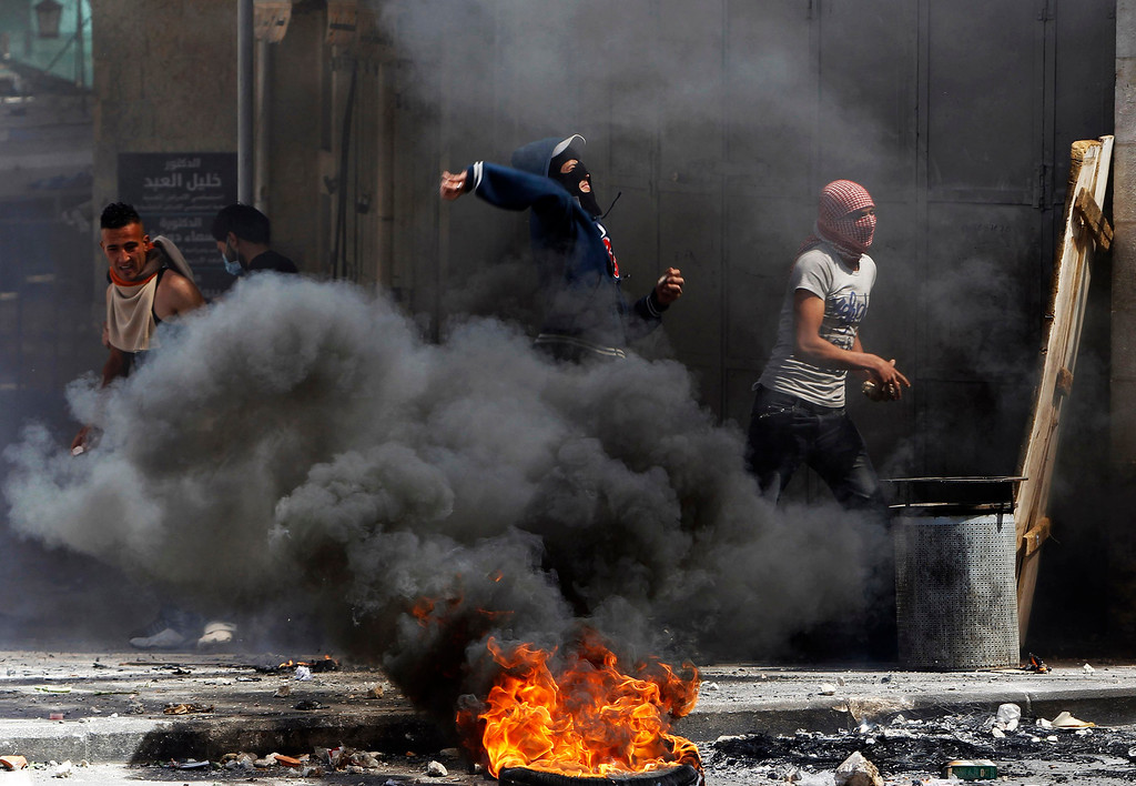 . Palestinian protesters throw stones near a burning tyre during clashes with Israeli soldiers in the West Bank city of Hebron, after Maysara Abu Hamdeya, a Palestinian inmate died from cancer in an Israeli hospital on Tuesday April 2, 2013. Hamdeya\'s death threatened to raise tensions in the Israeli-occupied West Bank, where Palestinians, who view jailed brethren as heroes in a fight for statehood, have held several protests in recent weeks in support of prisoners. REUTERS/Ammar Awad