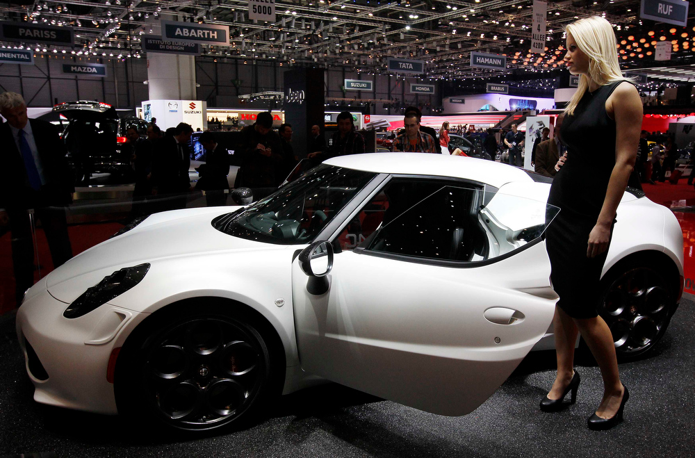 . A model stands next to the Alfa Romeo 4C displayed on the company\'s booth during the first media day of the Geneva Auto Show at the Palexpo in Geneva  March 5, 2013. The Geneva Motor Show will take place from March 7 to 17, 2017. REUTERS/Denis Balibouse