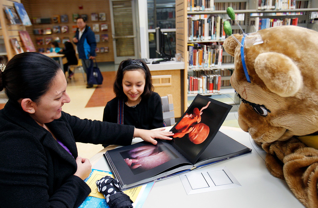 . From left, the San Jose Public LIbrary Mascot Conroy the Cougar read with Yvette Echeverria, 11,  Norma Chacon at the Seven Trees Branch Library after its grand opening celebration, in San Jose, Calif. on Saturday, January 26, 2013.   (LiPo Ching/Staff)